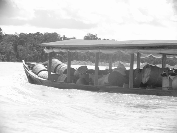 Gasoline is carried up the Madre de Dios River in Peru in small boats to supply the generators used to pump water from the river onto sluice beds used for gold mining. Behind the boat you can see mounds of sediment that has been mined for gold, a dangerous obstacle for subsequent boat travel. Photo by Mrinalini Erkenswick Watsa