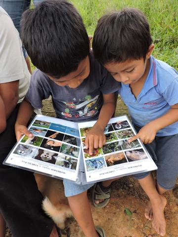 Local boys enjoy looking at photos of wildlife. Photo by: Diana Alvira.