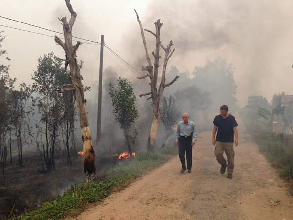 VICE correspondent Ben Anderson with conservationist Mike Griffiths walking in a hazy Indonesian village. Credit: Jackson Fager/HBO