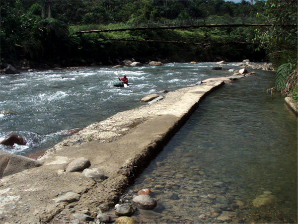 Roberto Carrera paddles by this sustainable, free-flowing diversion structure for a small hydroelectric project on the Misahuallí River in the Napo Province of Ecuador. It was built many years ago without heavy equipment or machinery and still operates today.