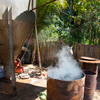 Men burn charcoal that has been added to the slurry as a final step to recover final traces of gold. The residual mercury also burns off and is emitted into the air. (Lombok)