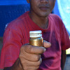 A man holds up a vial of mercury bought in Medan, a city in northern Sumatra. Mercury costs 1.7 million rupiah per kilo.