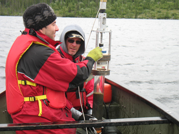 Researchers Andrew Paterson and Chris Jones with a freshly extracted lake sediment core. Photo by: Bill Keller.