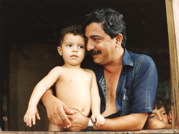 Chico Mendes in the window of his home in Xapuri, Brazil with Sandino, his son, in November 1988. Photo by Miranda Smith, Miranda Productions, Inc.