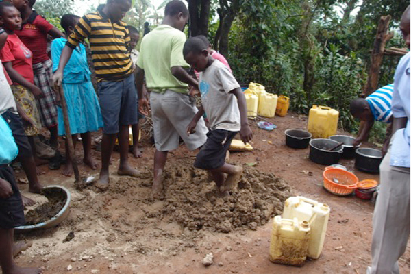 Students mix the clay for the bricks with their feet. Photo courtesy of Kasiisi Project / Camp Uganda.