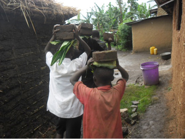 Carrying the dried bricks to a house to be built into a stove. Photo courtesy of Kasiisi Project / Camp Uganda.