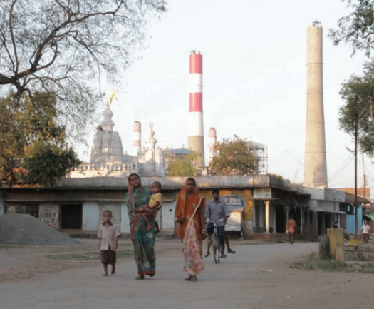 Local residents walk in front of a coal plant. Photo by: Goldman Environmental Prize.