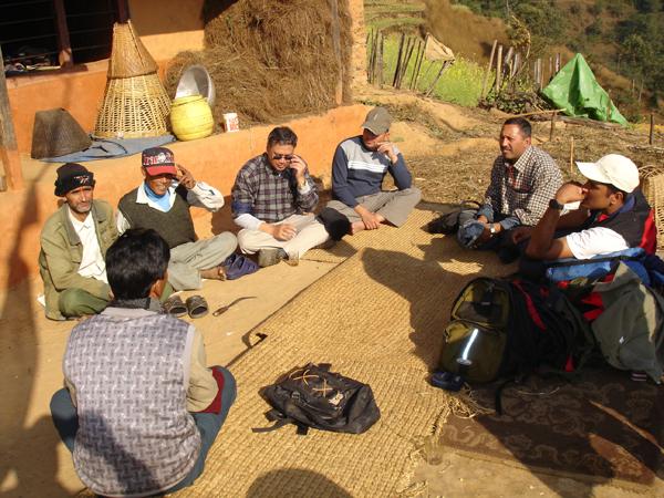Agrawal ha dedicado su carrera a buscar qué elementos permiten que los medios de vida de la gente coexistan con los bosques sostenibles. Aquí podemos ver a miembros de la comunidad sentados para un debate. Foto de la Red IFRI de la Universidad de Michigan.