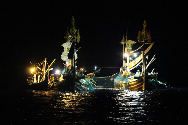 Paired purse seiners make a late-night haul in the Bali Strait with a support boat strapped alongside.  Regional fishery ministry officials say they are trying to crack down on the practice of holding multiple boats under a single license. Photo copyright © 2014 Melati Kaye.