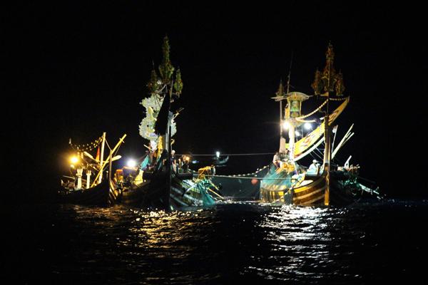 Pescherecci in coppia pescano a notte fonda nello Stretto di Bali con una barca di supporto legata al fianco. I funzionari regionali del Ministero della Pesca dicono che stanno cercando di inasprire i controlli sulla pratica di mantenere più barche sotto una singola licenza. Foto di Melati Kaye (2014).
