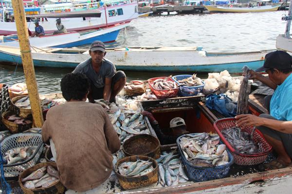 Dei pescatori scaricano la pesca di una settimana presso un porto a Makassar. Foto di Melati Kaye (2014).