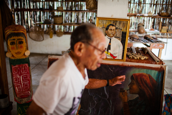 Don Jesús Smith stands in front of a painting of his grandfather, Kuna revolutionary hero Nele Kantule, while talking to students about artifacts in the Olomaili Museum on Ustupu Island.