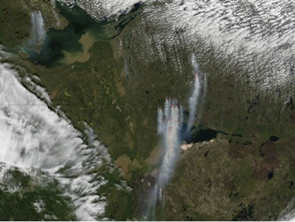 Plumes of smoke blow south towards a patch of blackened earth left by the Richardson fire in 2011. Clusters of wildfires are outlined in red in this image taken by the Moderate Resolution Imaging Spectroradiometer (MODIS). Image courtesy of NASA.