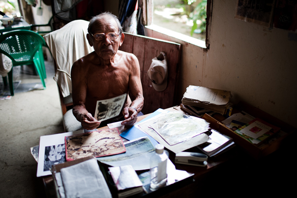 Don Jesús Smith looks through old photos at the desk in his home on Ustupu Island. Don Jesús is the grandson of the Kuna revolutionary leader, Nele Kantule, and an outspoken advocate and teacher who is trying to ensure that young Kuna boys and girls learn about their culture.