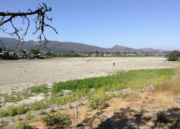 Man walking in dry lake bed. Laguna Lake, San Luis Obispo, California. Photo courtesy of Creative Commons/2.0