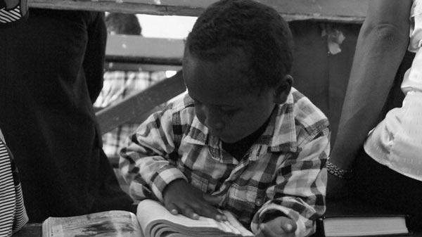 A boy focuses on a bible during the Sunday tradition for many Fijians of attending mass.  Photo by Amy West
