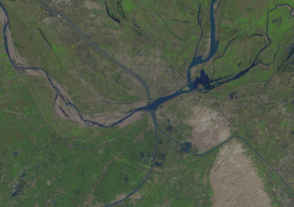 This Landsat image shows the Sukkur irrigation dam (center) on the Indus River diverting water into several canals and sharply reducing downstream flows (left). The dam was completed in 1932, yet dolphins still live in the river downstream. Image credit: U.S. Geological Survey.