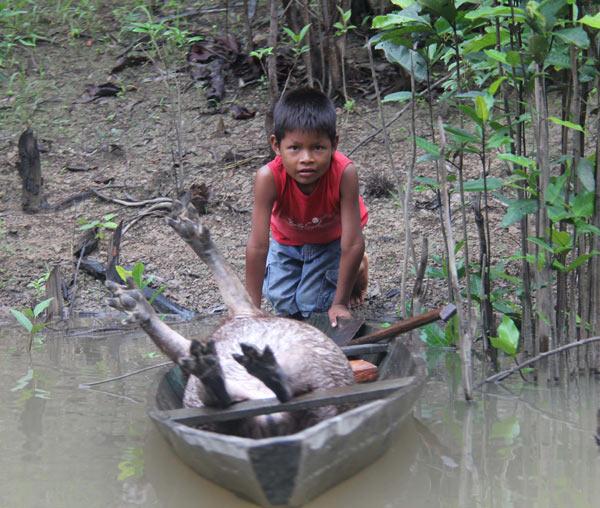 Un joven cazador vuelve a casa con su presa por el Río Ampiyacu en la región de Loreto en Perú. Foto por Barbara Fraser