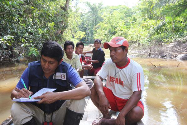 El periodista kukama Leonardo Tello conduce una entrevista mientras viaja por bote a lo largo de un canal del Río Marañón en el nordeste de Perú. Foto por Barbara Fraser