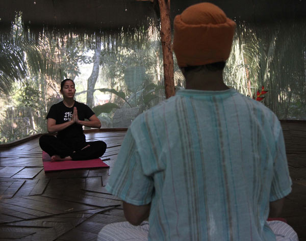 Days at the Kapievi Ecovillage begin with yoga against a backdrop of trees and bird calls. Photo by Barbara Fraser.