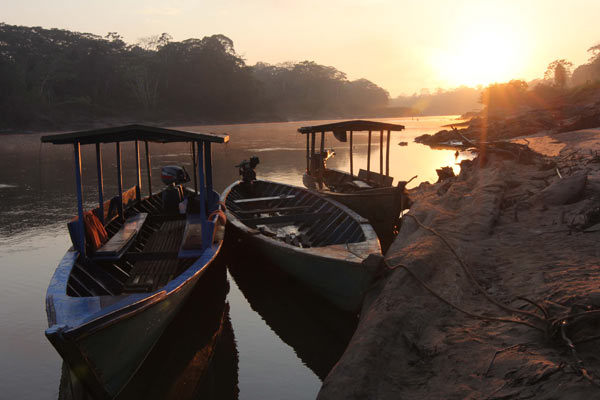 Sunset silhouettes boats on the Tambopata River at El Gato, a community-based tourism operation in Peru's Madre de Dios region. Photo by Barbara Fraser.