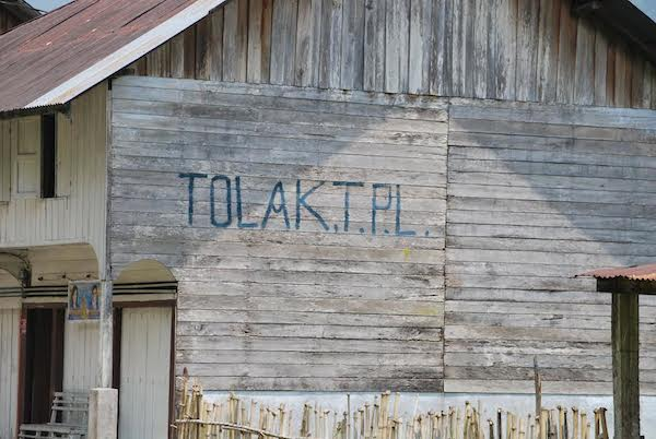 Graffiti on the side of a building not far from TPL's switch mill in North Sumatra translates to
