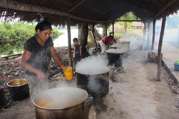 Women boil down fruit from the palm known as aguaje (Mauritia flexuosa) for oil in San José de Parinari, a community inside Peru's Pacaya-Samiria National Reserve. The oil is sold for use in cosmetics. Photo credit: Barbara Fraser.