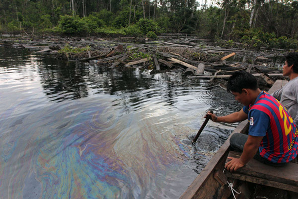 CUNINICO, Peru--Villager examine oil slick near this Kukama Indian village in the northeastern Peruvian Amazon. Photo by Barbara Fraser.