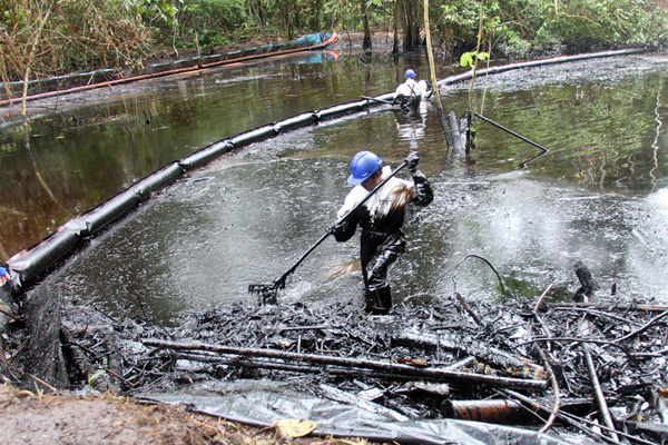 Workers clean up a 7,800-barrel oil spill in the community of San Pedro, a Kukama Indian village