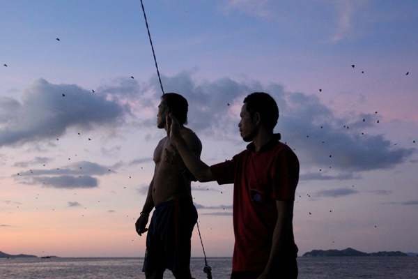 Local men watch the flying fox show. Photo by: Tiffany Roufs.