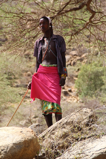 After spending most of the day on foot, a member of the Borana tribe stands watching over his herd of cattle as they eagerly drink water.  Photo by Nika Levikov/Marwell Wildlife.
