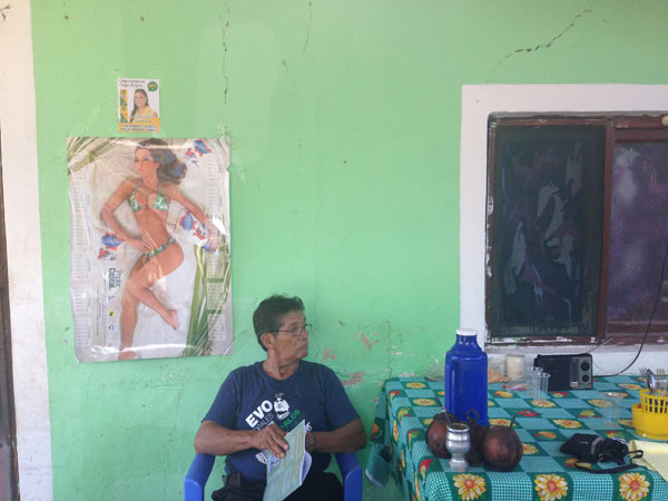 Celudonio Corumeche sits in front of poster given to him by the sugar processing company for which he used to work. Above the poster is an advertisement for a local political candidate from the opposition, but Corumeche wears a shirt depicting Evo Morales, which was given out by a local candidate for the governing party. Photo credit: Alexandria Ellerbeck.