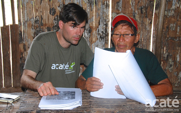 Chris Herndon (left) and Arturo, a shaman (right), look over drafts of the new encyclopedia. Photo courtesy of Acaté.