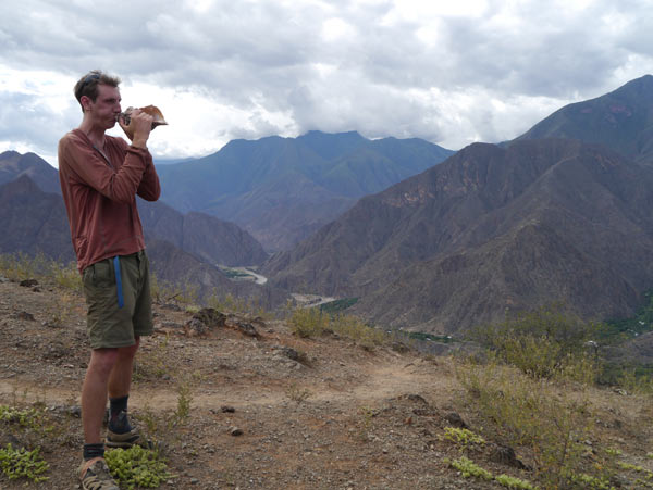 Benjamin Webb, on the long hike out, blows a conch shell in memory of Jhuliño. It was
