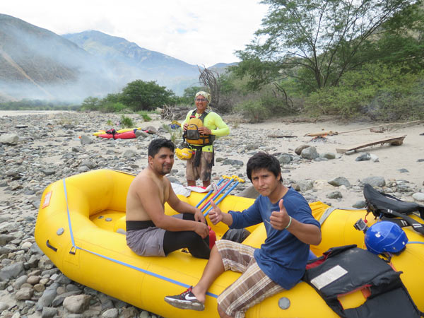This yellow raft is the one I went downriver in: its owner, Edgar Ramos, is seated left. Jhuliño gives a thumbs up. He was proud to join the Peruvian raft guides that accompanied Webb's expedition. Like most members of the Marañon river communities, the guides are tied together by shared loss – all have had friends killed by the river or in freak accidents getting to the river.  Photo Credit: Danielle Villasana.