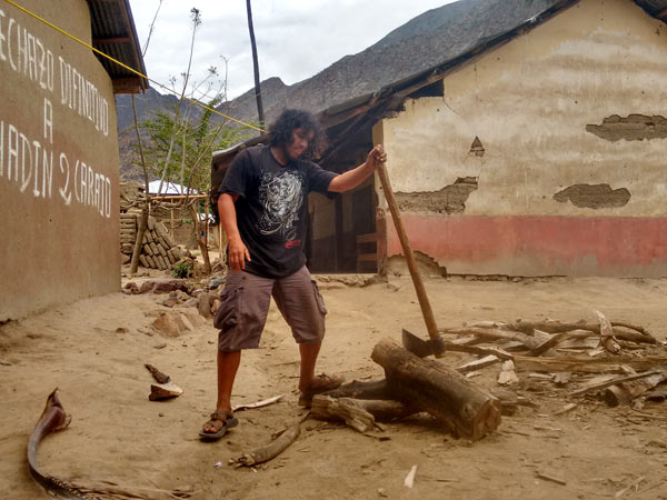 "The sport of rafting began to make the jump to Peruvians in the 1980s, and spread as local guides and rafting enthusiasts, with equipment donated or bought secondhand from foreigners, introduced their friends to the sport. Jhuliño would spend three months living at the house of Pedro Peña, pictured here by the Huaman family house in Tupen, chopping wood for the cookfire. The graffiti in the background says, ""I definitively reject Chadin II.""  Photo credit: Saul Elbein"