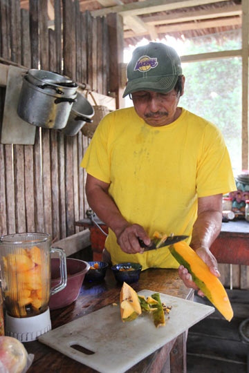 Eduardo Ramírez prepares fruit in the kitchen at El Gato, a community-based tourism operation in Peru's Madre de Dios region. Photo by Barbara Fraser.