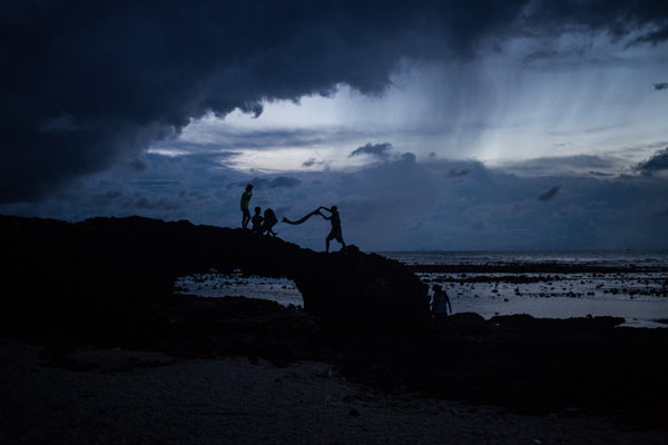 A group of friends wrap up their camp as a storm blows into Ly Son Island. A fisherman cleans his net off the coast of Ly Son Island in Vietnam. Recent tensions with China have forced fishermen to work closer to shore, which has dramatically impacted biomass in the region.