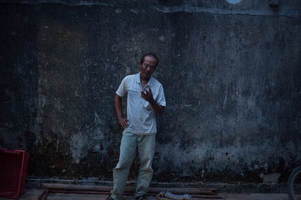 Nguyen Phu smokes a cigarette outside his home on Ly Son island. In 2007 Phu was arrested by a Chinese military vessel while fishing off the coast of Vietnam. According to Phu he endured beatings and severe conditions because the Chinese said he'd violated their sovereign waters.