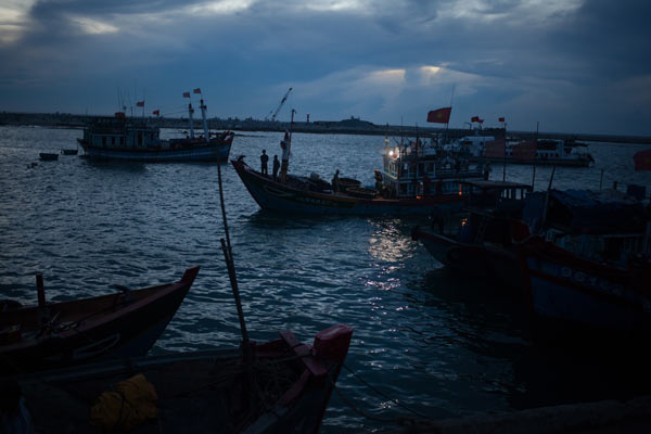 Fishing vessels return from sea at dawn.