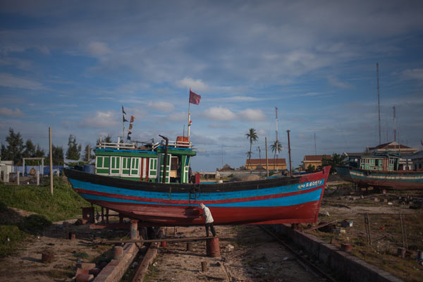 A man repaints his fishing boat.