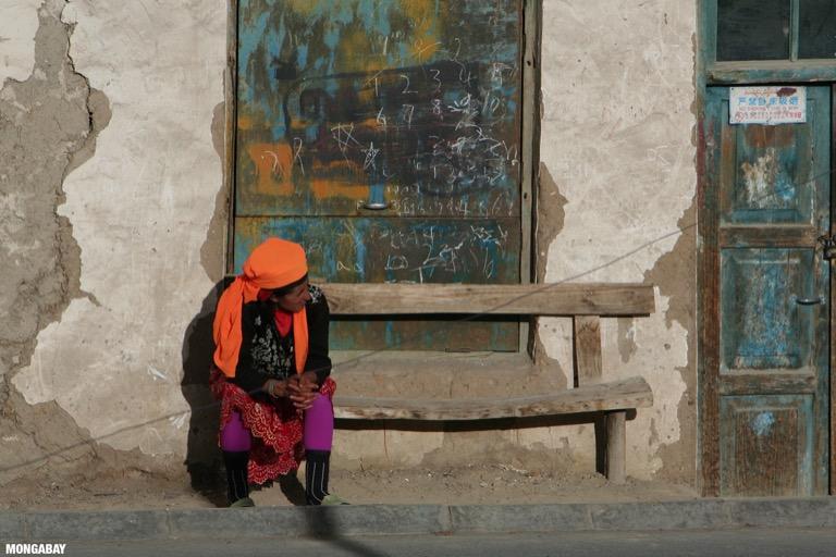 Tajik woman sitting on a bench in front of a shuttered window in Tashkurgan