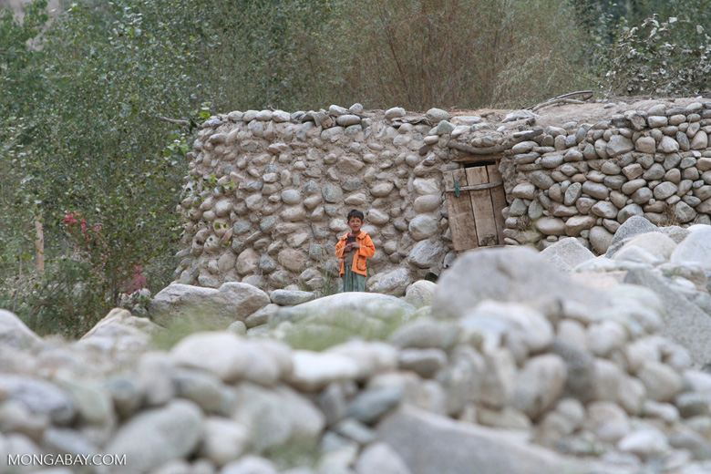 Tajik boy in an orange jacket standing in front of his stone home