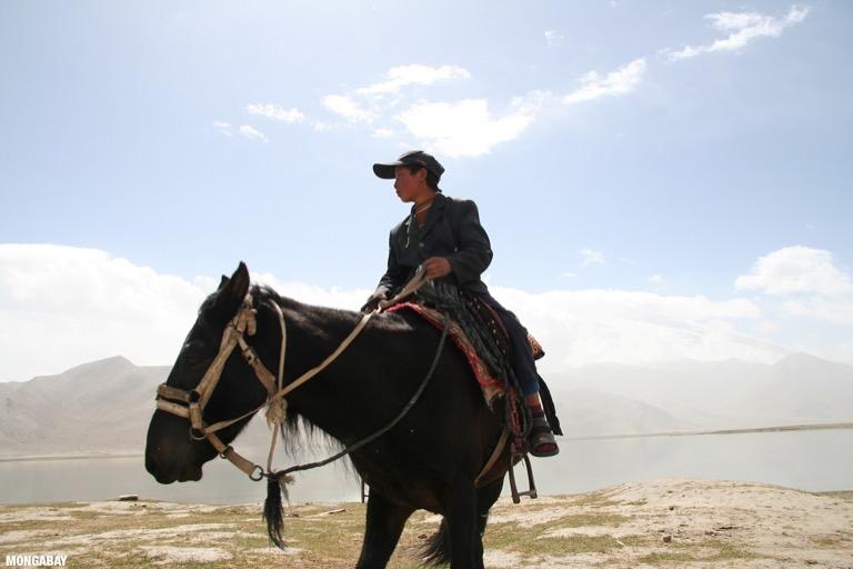 Uygur boy on horseback at Karakul Lake