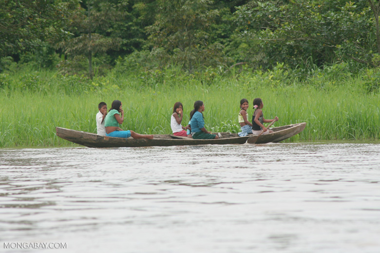 Group of Amerindian girls in a dugout canoe on the Amazon river