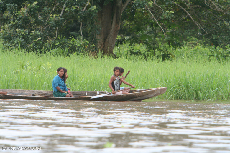 Girls paddling a dugout canoe in the Amazon
