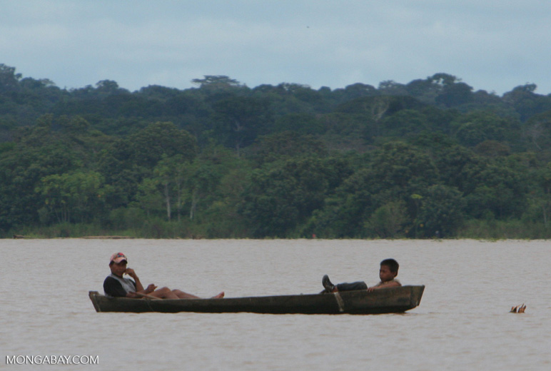 Two boys sitting in a dugout on the Amazon river