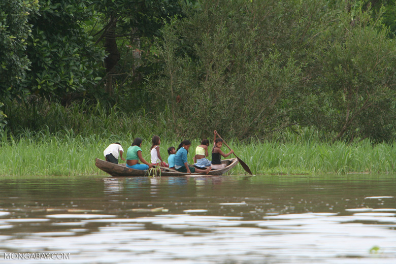 Group of local girls paddling a dugout canoe in the Amazon