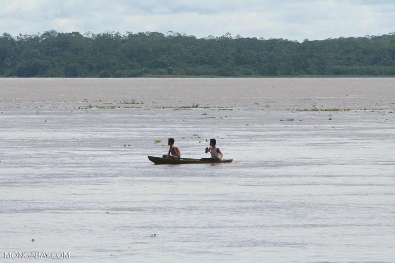 Two men in a dugout canoe on the Amazon river