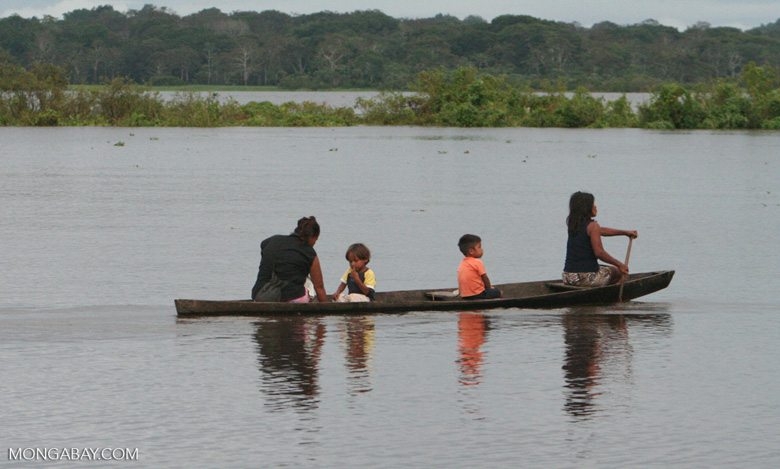 Mothers and sons in a dugout on the Amazon